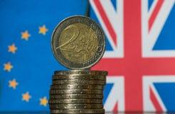 Las monedas euro con británico y el europeo señalan el fondo por medio de una bandera Imagen de archivo libre de regalías