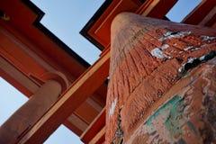 Las monedas japonesas (yenes, JPY) sticked al polo de madera de la puerta de Myiajima (el torii gigante de Itsukushima) foto de archivo libre de regalías