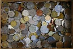 Las monedas mezclaron la colección, recolectada en una caja de madera fotos de archivo