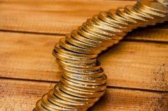 Las monedas se cierran para arriba en fondo de madera fotografía de archivo libre de regalías