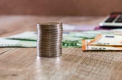 Las monedas se cierran para arriba en un fondo del euro, de dólares y de la calculadora foto de archivo