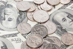 Las monedas sobre cientos cuentas de dólar se cierran encima de la visión Fotografía de archivo libre de regalías
