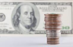 Las monedas sobre cientos cuentas de dólar se cierran encima de la visión Imagen de archivo