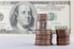 Las monedas sobre cientos cuentas de dólar se cierran encima de la visión Imagen de archivo libre de regalías
