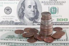 Las monedas sobre cientos cuentas de dólar se cierran encima de la visión Fotos de archivo libres de regalías
