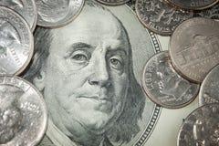 Las monedas sobre cuentas de dólar se cierran encima de la visión Imagen de archivo