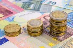 Las monedas trazan en billetes de banco euro Imágenes de archivo libres de regalías