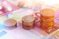 Las monedas trazan en billetes de banco euro Fotografía de archivo
