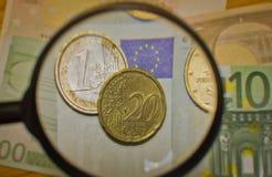 Las monedas y los billetes de banco aumentaron la lupa Fotografía de archivo