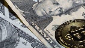 Las monedas y los billetes de dólar de Bitcoin giran en la tabla almacen de metraje de vídeo