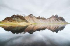 Las montañas asombrosas reflejaron en el agua en la puesta del sol Stoksnes, Islandia Foto de archivo libre de regalías