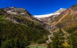 Las montañas coronadas de nieve en el Bernina se extienden de Alp Grum en verano Fotos de archivo