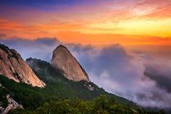 Las montañas de Bukhansan son cubiertas por la niebla y la salida del sol de la mañana fotografía de archivo