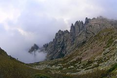 Las montañas de Córcega, rocas agudas en las nubes, emigrando la ruta GR-20 Imagen de archivo