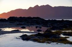 Las montañas de la isla de Vancouver en la puesta del sol, rocas en el primero plano fotos de archivo libres de regalías