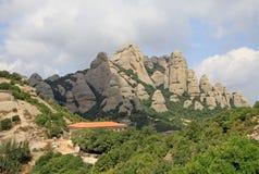 Las montañas de Montserrat acercan a la abadía benedictina Santa Maria de Montserrat en Monistrol de Montserrat, España Imagen de archivo