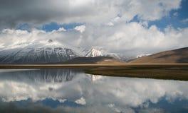 Las montañas de Sibillini reflejaron en el agua en Umbría foto de archivo