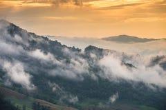 Las montañas en la niebla cuando la puesta del sol Imágenes de archivo libres de regalías