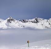Las montañas en niebla y la advertencia cantan en cuesta fuera de pista Fotos de archivo