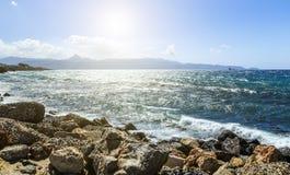 Las montañas hermosas inspiradas ajardinan con el mar, la costa, la playa y las rocas, altas montañas en fondo en la salida del s Foto de archivo