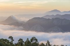 Las montañas majestuosas ajardinan debajo del cielo de la mañana con las nubes niebla fotografía de archivo libre de regalías