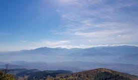 Las montañas siluetean a través de la niebla con horizonte hermoso imagenes de archivo
