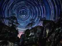 Las montañas y los árboles en fondo estrellado con las estrellas brillantes se arrastran Fotos de archivo libres de regalías