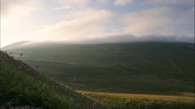 Las montañas y las nubes verdes en cielo sobre picos cubrieron el bosque verde, timelapse almacen de video