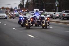 Las motocicletas de la policía escoltan un coche fúnebre fotografía de archivo