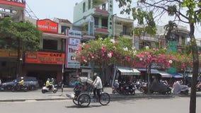 Las motos, los carritos y los autobuses viajan a través de las calles estrechas de Vietnam la bandera festiva vuela en el cuadrad almacen de metraje de vídeo