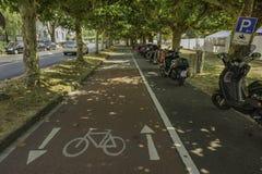 Las motos parquearon a lo largo de un carril del ciclo cubierto por los árboles en Dusseld foto de archivo