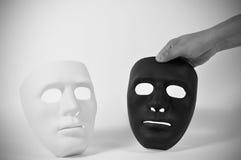 Las máscaras blancos y negros les gusta la conducta humana, concepto Fotos de archivo libres de regalías