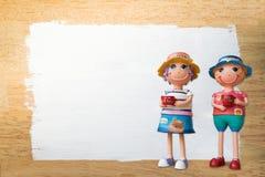 Las muñecas de cerámica que sostenían la taza de café con blanco pintaron el backgro de madera Imágenes de archivo libres de regalías