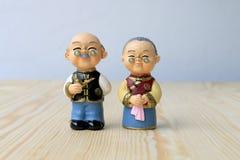 Las muñecas de la abuela y del abuelo en chino uniforman el estilo que se coloca en fondo de madera en Año Nuevo chino Fotografía de archivo libre de regalías
