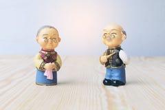 Las muñecas de la abuela y del abuelo en chino uniforman el estilo que se coloca en fondo de madera en Año Nuevo chino Foto de archivo