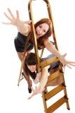 Las muchachas acercan al step-ladder fotos de archivo