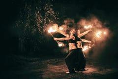 Las muchachas activas realizan los trucos para la demostración del fuego en la noche Foto de archivo