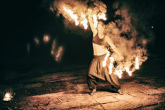 Las muchachas activas realizan los trucos para la demostración del fuego en la noche Imagenes de archivo