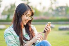 Las muchachas adolescentes asiáticas juegan smartphone en el césped Ella está llevando el Br Fotografía de archivo