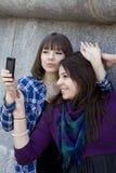 Las muchachas adolescentes atractivas jovenes toman cuadros por el teléfono Imágenes de archivo libres de regalías