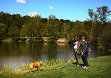 Las muchachas adolescentes con el perro caminan en parque europeo de la ciudad con los árboles y el lago Imagenes de archivo