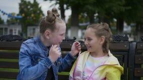Las muchachas adolescentes consideran los pendientes en los oídos de cada uno que se sientan en banco en parque de la ciudad metrajes