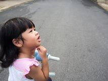Las muchachas asiáticas montan una bicicleta y el pensamiento, su cara mira al sospechoso y tiene preguntas foto de archivo