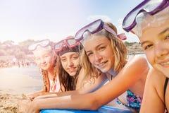 Las muchachas asolean broncear en la playa después de bucear Fotografía de archivo