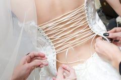 Las muchachas atan para arriba una alineada de la novia Imagen de archivo libre de regalías