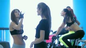 Las muchachas atléticas con el cuerpo atractivo abren la botella de agua metrajes