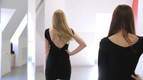 Las muchachas atractivas entrenan para permanecer en la posición mitad-dada vuelta en estudio metrajes