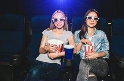 Las muchachas atractivas y encantadoras se están sentando en sillas en cine Cada uno de ellos tiene un diverso tamaño de cestas c Fotos de archivo