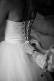 Las muchachas ayudan a la novia a abotonar el vestido de boda Fotografía de archivo libre de regalías
