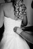 Las muchachas ayudan a la novia a abotonar el vestido de boda Imagen de archivo